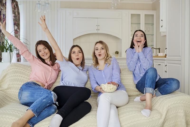 看电视的女孩,吃玉米花坐在ro的长沙发 库存图片