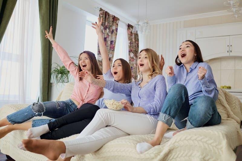 看电视的女孩,吃玉米花坐长沙发 库存图片