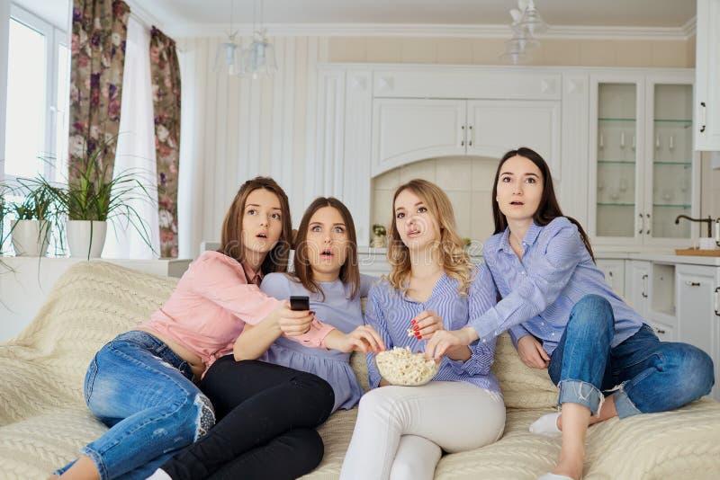 看电视的女孩,吃玉米花坐长沙发 库存照片