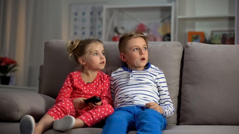 看电视的小孩子在父母捉住的晚上,娱乐 免版税库存图片