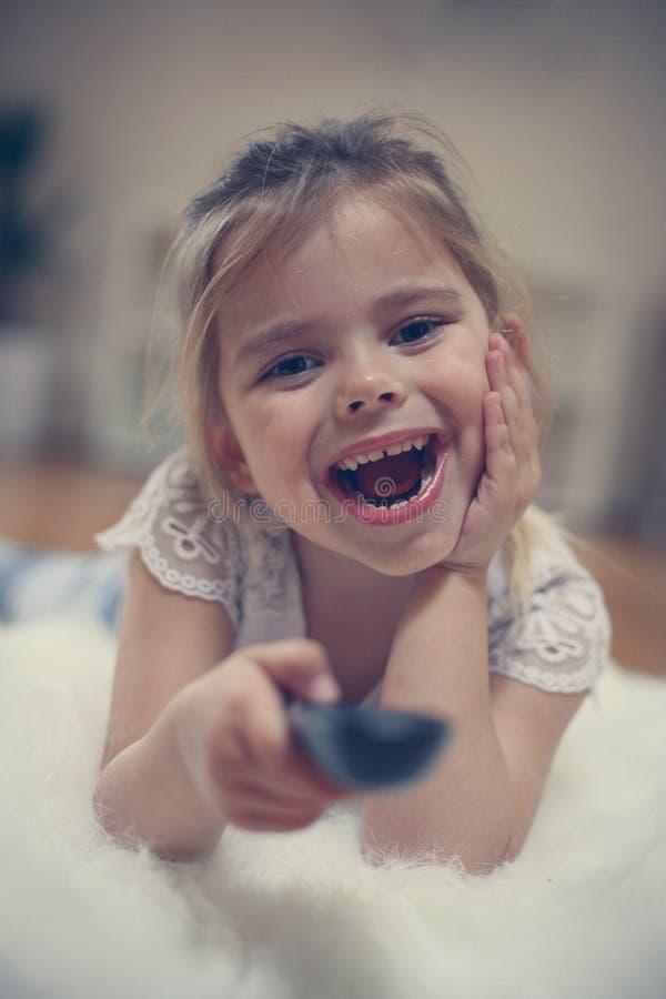 看电视的微笑的小女孩 关闭 库存照片