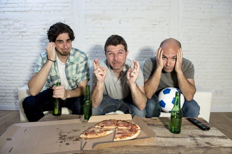 看电视的朋友狂热足球迷与啤酒瓶和薄饼痛苦重音配比 免版税图库摄影