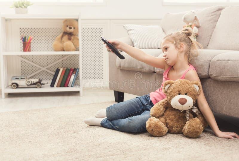 看电视的美丽的乏味小女孩 免版税库存照片