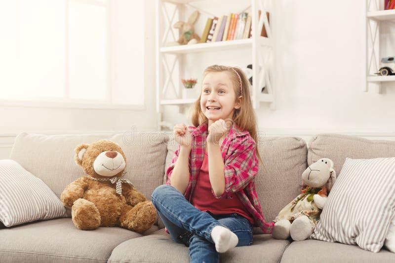 看电视的美丽的偶然小女孩,当在家时坐沙发 库存图片