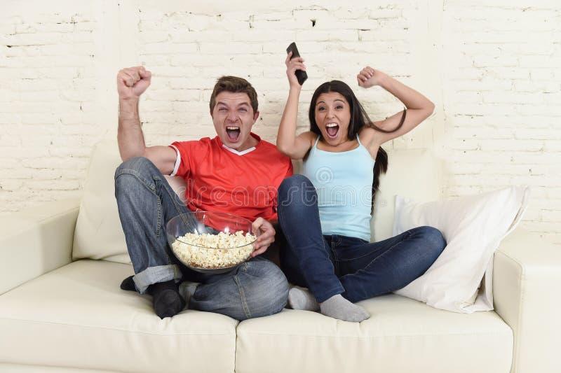 看电视的年轻夫妇炫耀橄榄球赛激动的庆祝 免版税库存图片