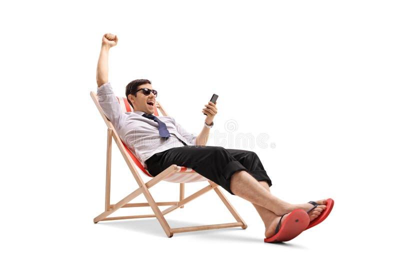 看电话和打手势幸福的商人 免版税图库摄影