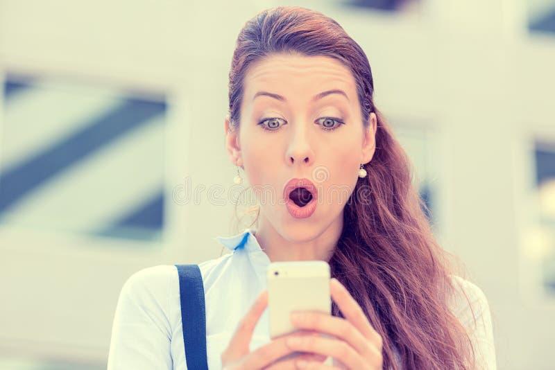看电话的急切女孩看见坏消息或照片激动令人厌恶的 图库摄影