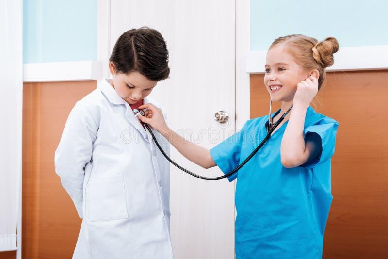看男孩的笑的女孩护士侧视图  免版税图库摄影