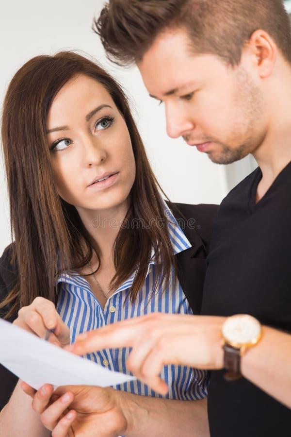看男性同事读书文件的女实业家 免版税库存照片