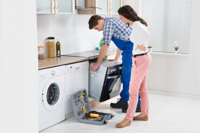 看男性工作者的妇女修理烤箱 免版税库存图片