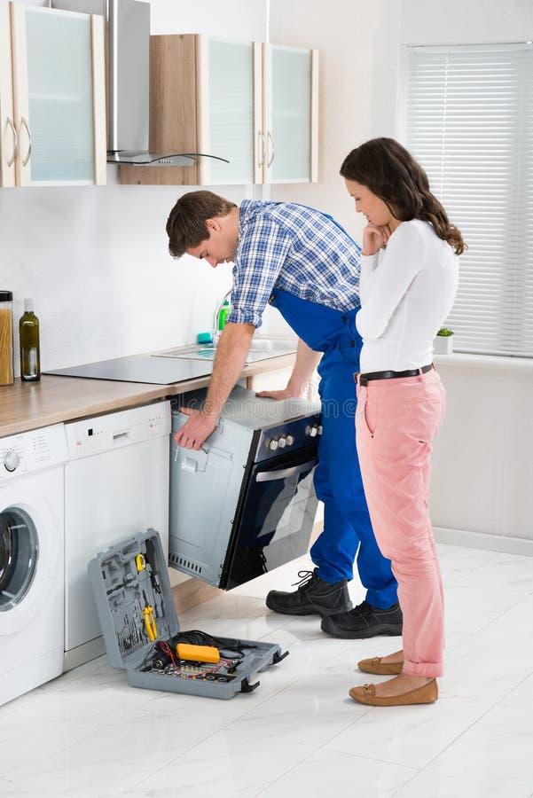 看男性工作者的妇女修理烤箱 库存照片