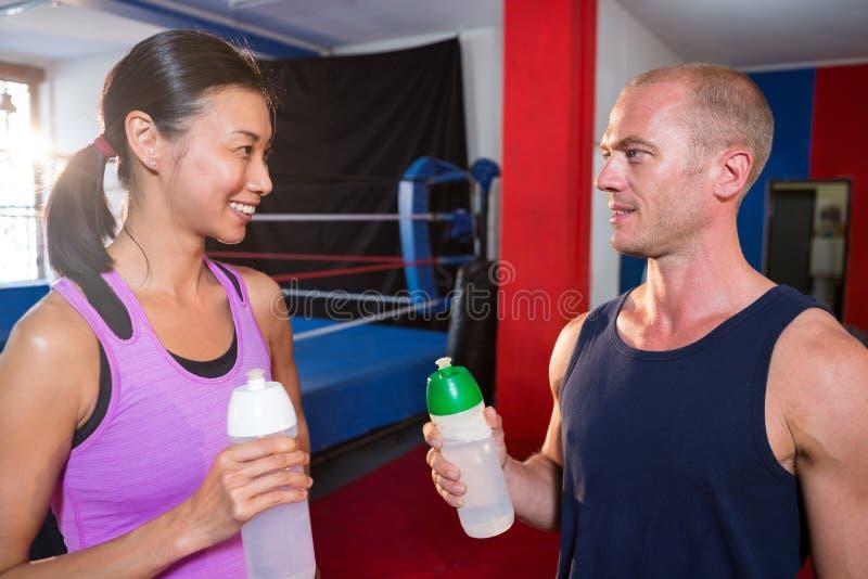 看男性的微笑的年轻女运动员,当拿着水瓶时 免版税库存图片