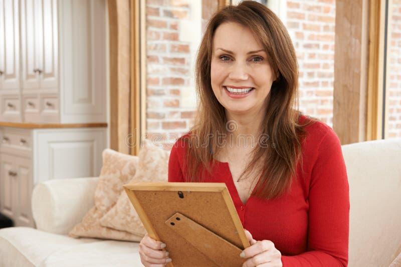 看画框的微笑的成熟妇女画象Hom 库存图片