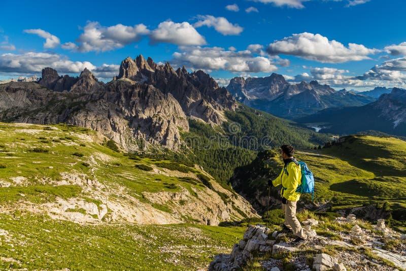 看白云岩山脉的庄严看法男性亚裔徒步旅行者在特雷Cime di Lavaredo足迹 库存照片