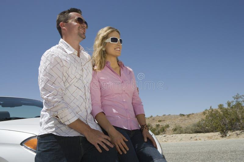 看的夫妇倾斜在汽车和  免版税库存照片