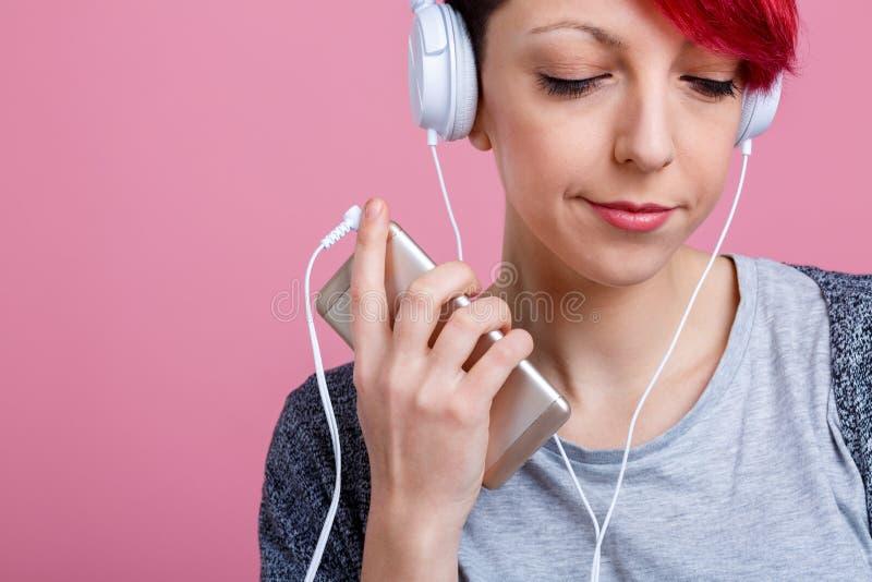 看的女孩听到在耳机的音乐有电话的和下来 在桃红色背景 特写镜头 免版税图库摄影