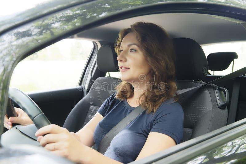 看的妇女驾驶汽车和外面 免版税库存照片