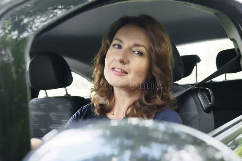 看的妇女驾驶汽车和外面 免版税图库摄影
