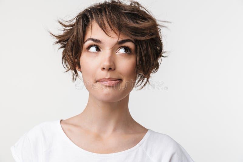 看的端庄的妇女画象特写镜头有短的棕色头发的在基本的T恤杉微笑和在旁边 免版税图库摄影