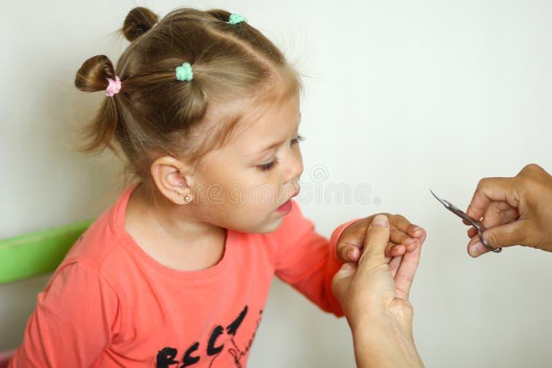 看的逗人喜爱的女孩整理她的指甲盖由修指甲剪刀 库存照片