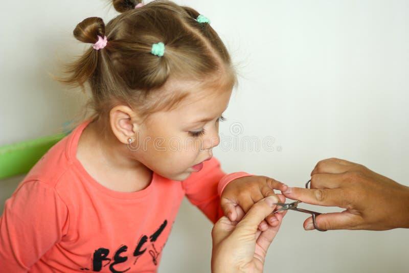 看的逗人喜爱的女孩整理她的指甲盖由修指甲剪刀 库存图片
