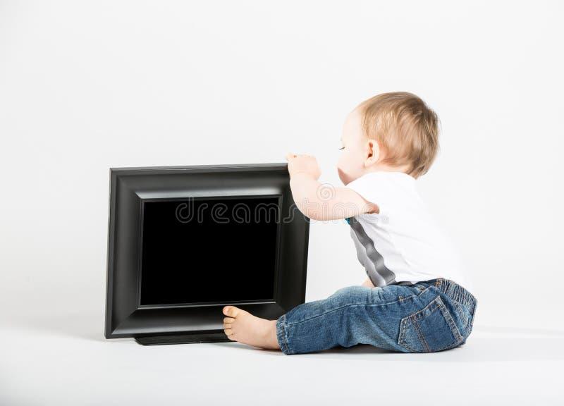 看的婴孩坐在画框旁边和后边 图库摄影