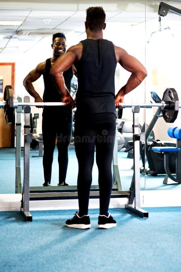 看的年轻肌肉人入镜子 免版税图库摄影