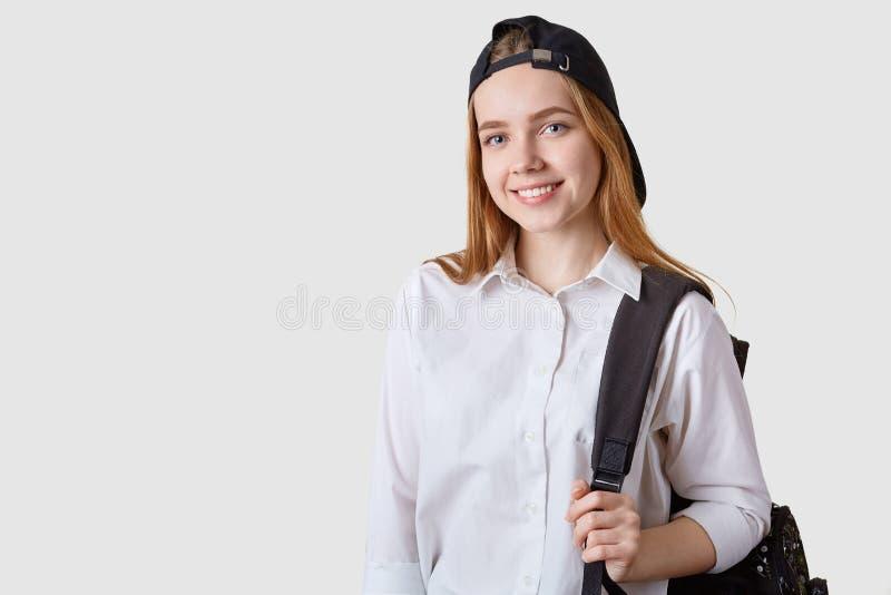 看直接地与迷人的微笑的照相机的学校女孩的图象,摆在隔绝在与黑bagpack的白色背景, 库存图片