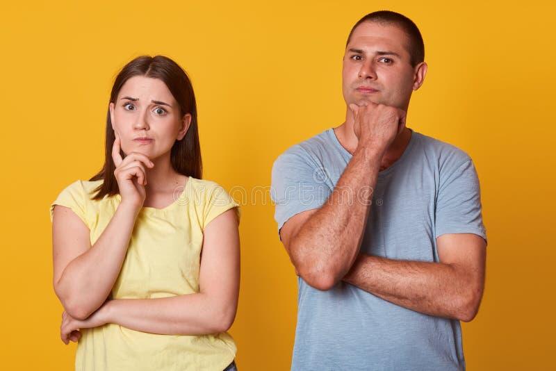 看直接地照相机,摆在的周道的美好的夫妇被隔绝在黄色背景在演播室,投入手接近 免版税图库摄影