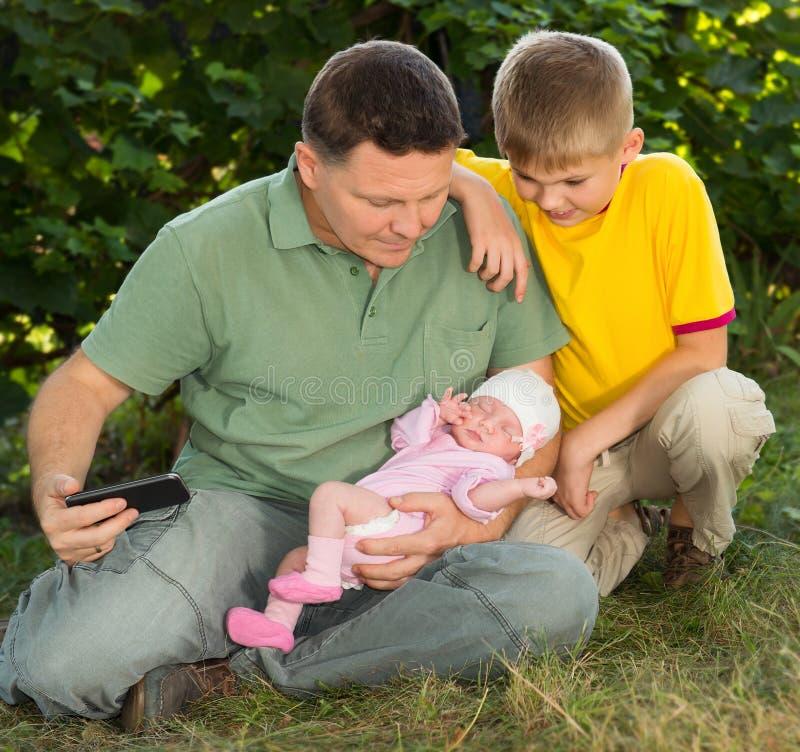 看睡觉的华美的新出生的婴孩的微笑的父亲和儿子 库存图片