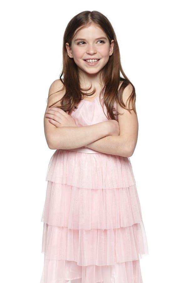 桃红色礼服的微笑的小女孩 免版税库存照片