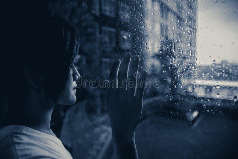 看窗口的哀伤妇女下雨下落 库存照片