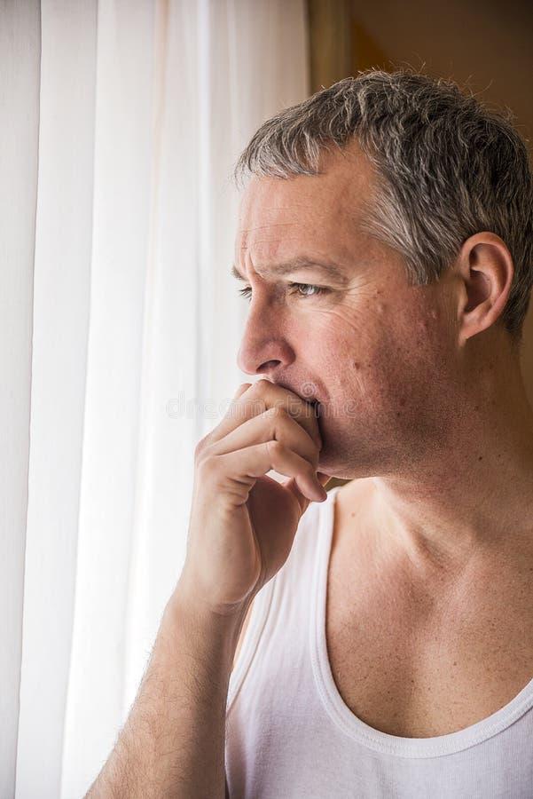 看窗口的哀伤的人 感到绝望 站立在窗口附近的沮丧的成熟人 库存图片