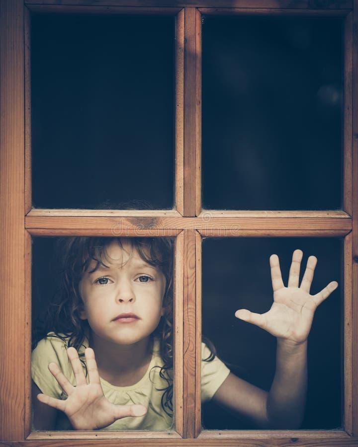 看窗口的哀伤的孩子 库存图片