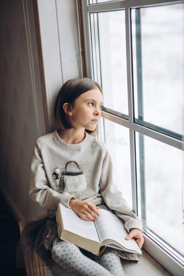看窗口的美丽的哀伤的不快乐的女孩,当基于窗台时 免版税库存图片