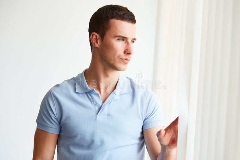 看窗口的英俊的人 库存图片