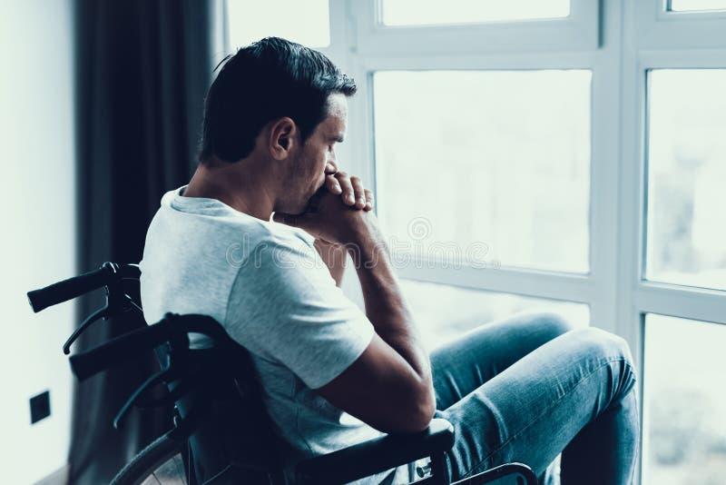 看窗口的轮椅的残疾人 库存照片