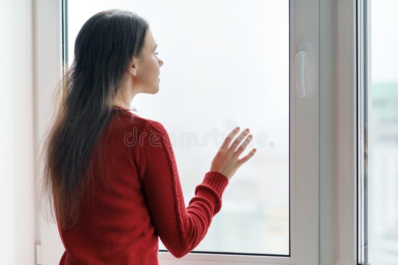 看窗口,女性的红色毛线衣的年轻女人在玻璃窗上把她的手,侧视图,窗口放在摩天大楼  免版税图库摄影