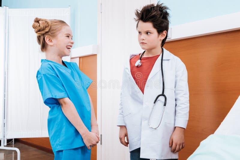 看笑的女孩的男孩医生 免版税库存照片