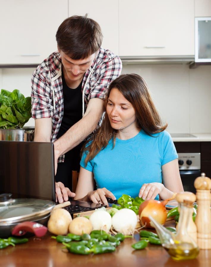 看笔记本的夫妇在烹调菜期间 免版税库存图片