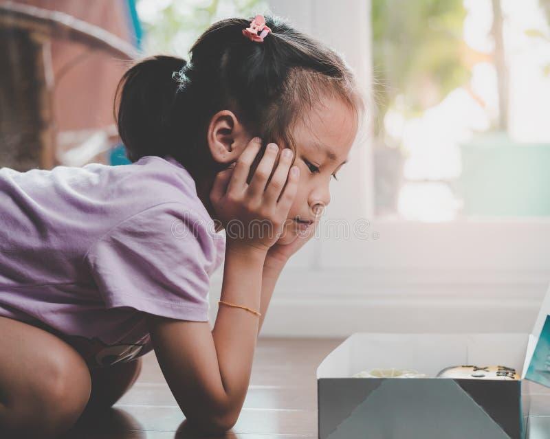 看箱子多福饼奇迹的女孩,如果她应该吃 免版税图库摄影