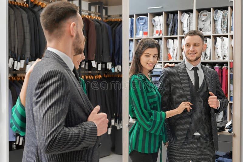 看精品店的镜子衣服的英俊的客户 免版税库存图片