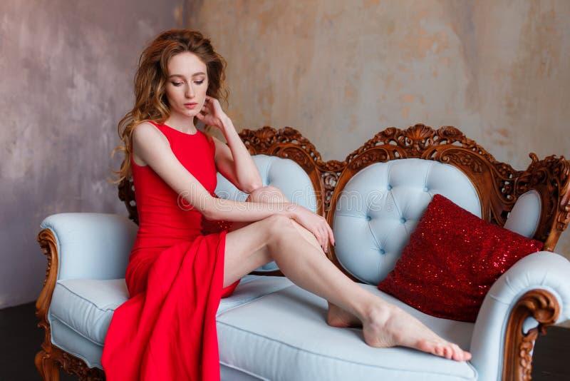 看红色A字型女装的礼服的性感的亭亭玉立的美丽的妇女说谎在豪华内部的沙发和下来 免版税库存照片