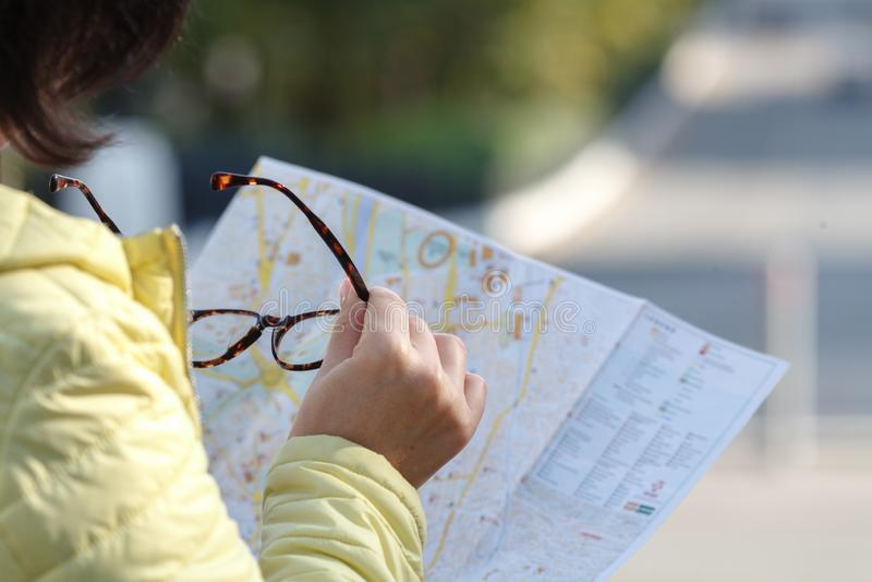 看纸地图的游人打电话 情感摆在正随风飘飞的雪木头的时装模特儿 库存图片