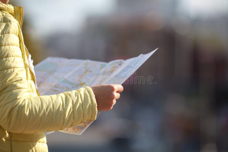 看纸地图的游人打电话 情感摆在正随风飘飞的雪木头的时装模特儿 免版税库存照片