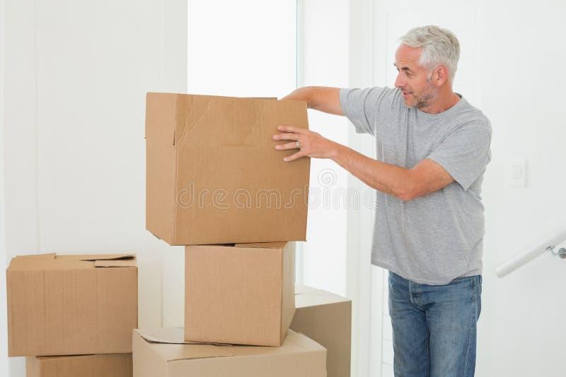 看纸板移动的箱子的微笑的人 库存图片