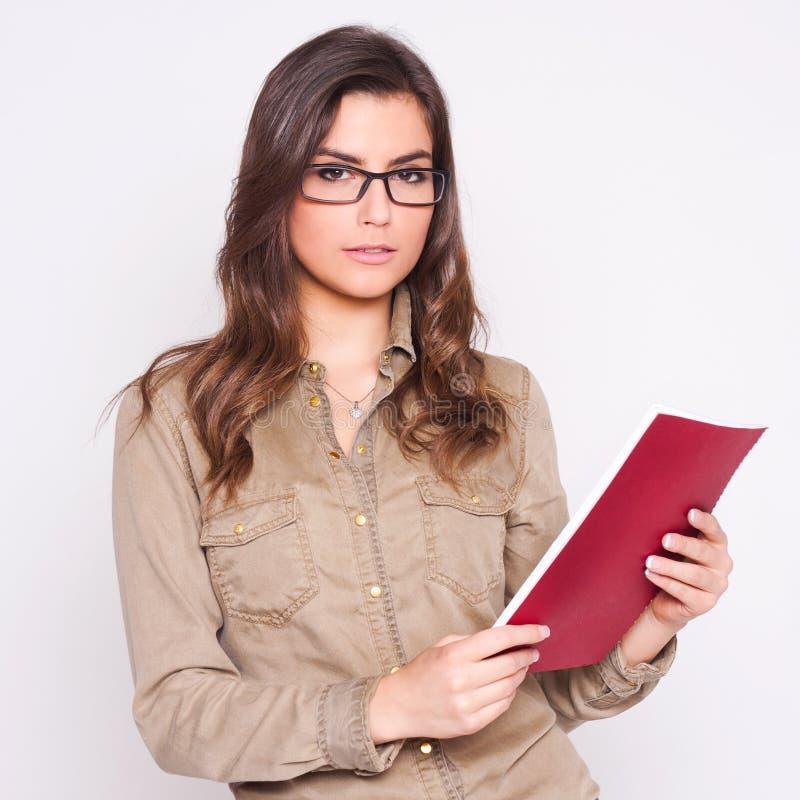 戴看纸的眼镜的美丽的女商人 免版税库存照片