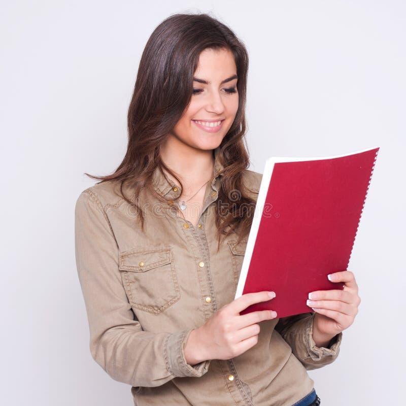 看纸的美丽的女商人,她微笑 图库摄影