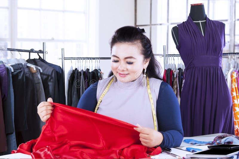 看纺织材料的时装设计师 免版税库存图片