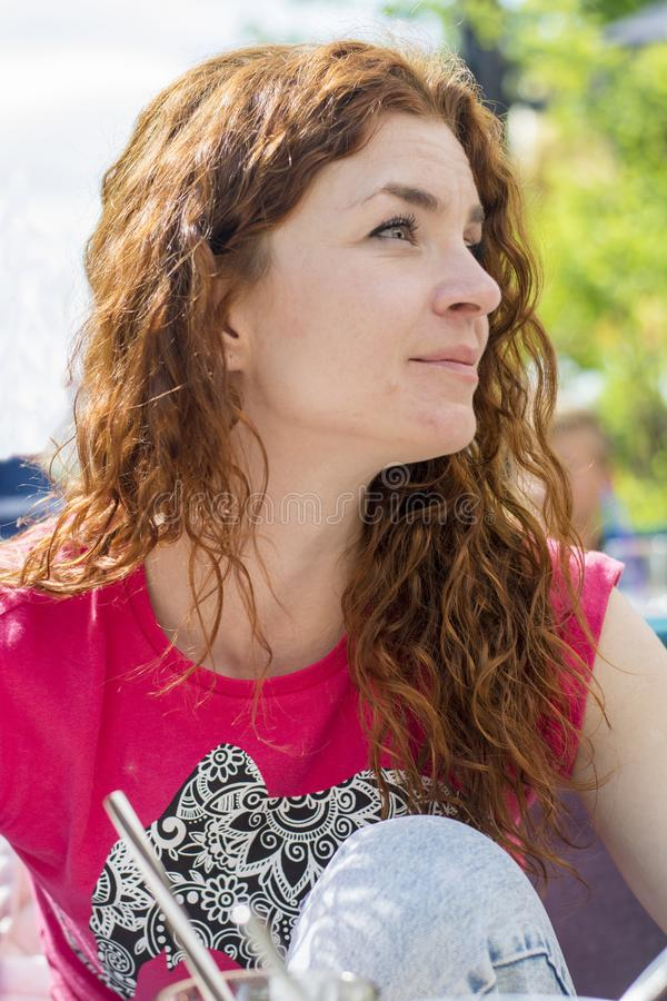 看美丽的红色头发的女孩某处 免版税库存照片